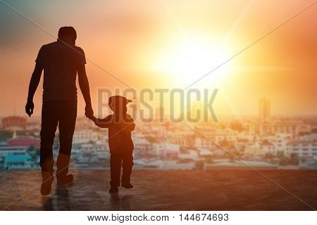Child holding an adult's hand. Father and son on a walk. silhouette concept.