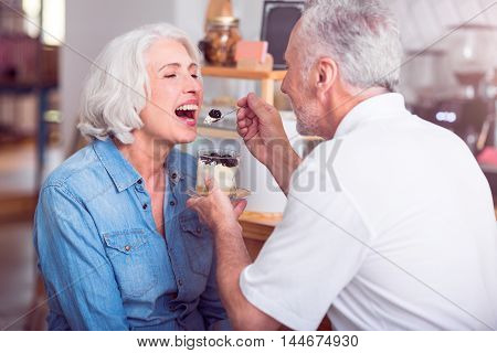 Love in little things. Positive delighted husband holding spoon and feeding her wife with dessert while sitting in the cafe