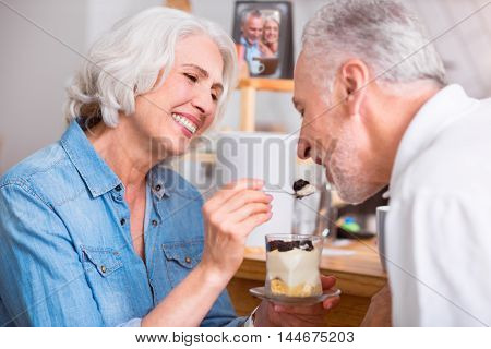 One spoon for you. Cheerful delighted senior smiling couple eating a dessert and having breakfast while resting in the cafe