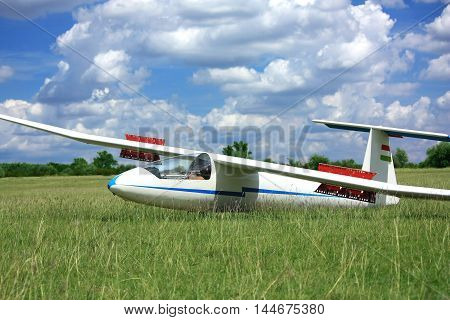 White glider airplane on runway grass with cloud sky