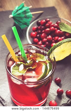 Fresh cranberry drink with lime and mint toned above