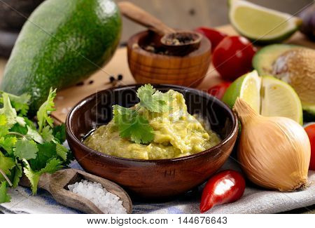 Homemade fresh guacamole sauce and ingredients on table