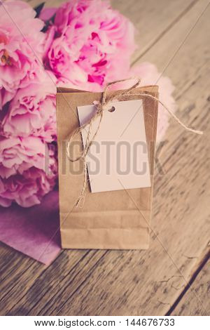 Kraft to pack gifts with a blank label for inscriptions or wishes on a wooden background next to a bouquet of flowers (Vintage)