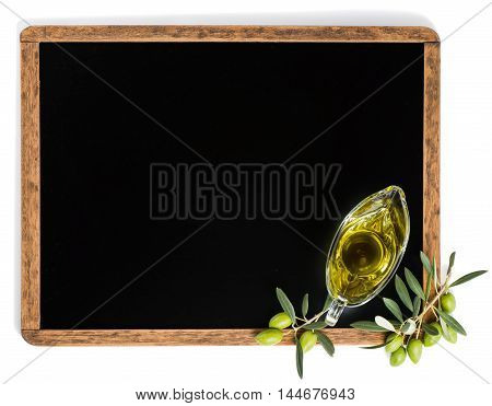 View from above of olive oil in a glass sauceboat and green olive fruits on a blackboard with copy space isolated on white background.