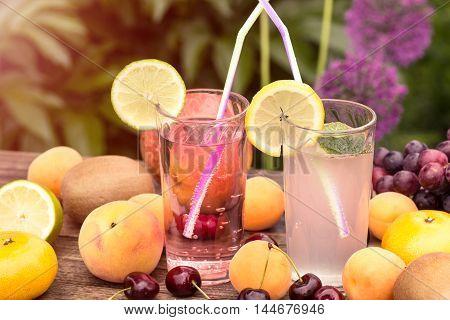 Fresh lemonade and ripe fruits outdoor shot
