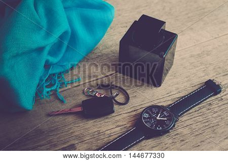 Men's Accessories. Men's fashion. Watches, scarf, perfume and key on wooden background (vintage)