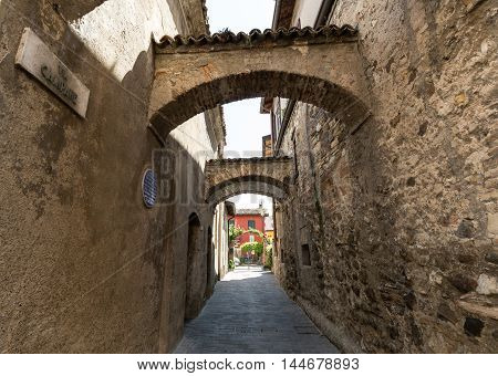 Picturesque narrow town street in Sirmione Lake Garda Italy.