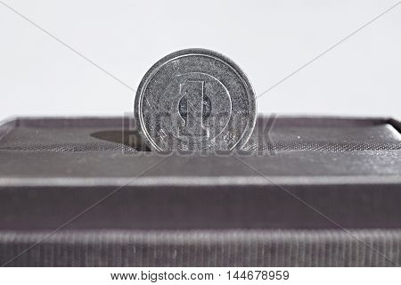 Macro detail of a silver coin of One Yen (Japanese Yen JPY) placed in the gray luxurious jewelry gift box as a symbol of luxury and highly appreciated Japanese currency