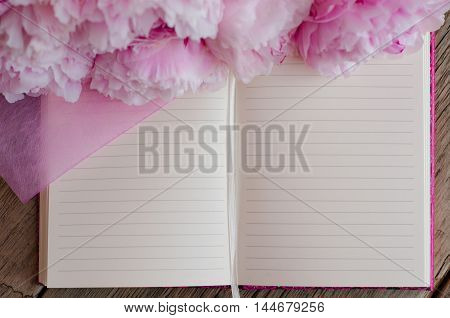 Open blank note pad decorated with pink peonies on a wooden background