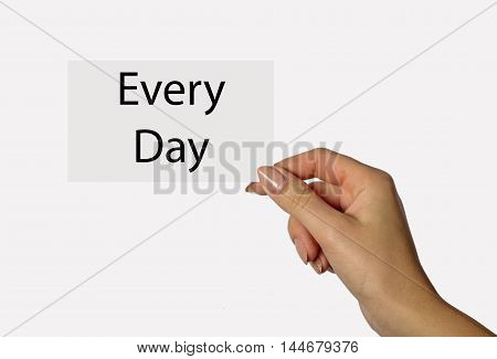 Beautiful hand of a young girl holding a card on a white background with the inscription Every Day