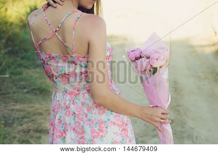 Girl in sundress with open back is holding a bouquet of peonies in a pink wrapper