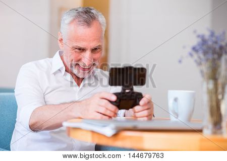 Time for hobby. Cheerful delighted senior man smiling and holding game console while resting in the cafe