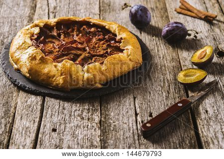 Homemade Rustic Plum Tart with cinnamon, galette on a rough wooden background. Selective focus. Toned