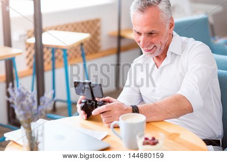 Involved in play. Cheerful senior man holding game console and playing while sitting at the table in the cafe