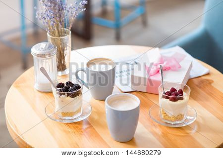Ready for breakfast. Close up of cups of coffee standing on the table near glasses with dessert