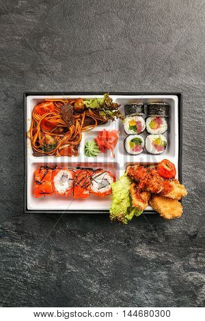 Bento Single portion takeout or home packed meal in Japanese cuision, top view in black stone