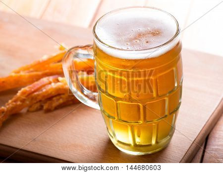 Glass of lager beer and snacks on wooden coaster