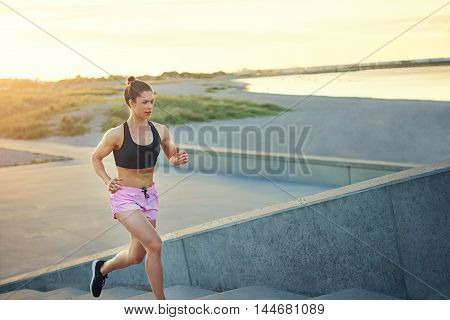 Toned healthy young woman out jogging running up a set of outdoor concrete steps with a lake or ocean lit by the morning sun in the background