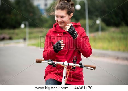 Young girl rides a Bicycle in a red jacket