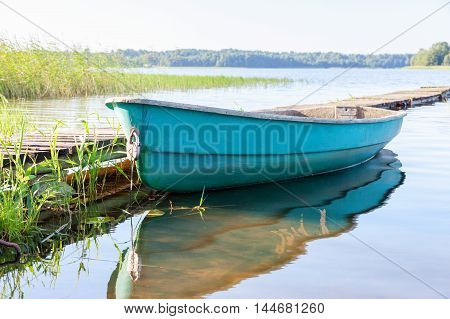 Fishing boat at the lake in the morning in summer sunny day