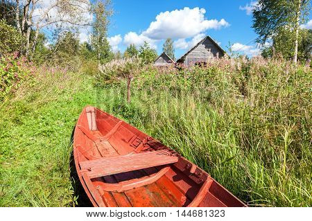 Old red wooden fishing boat at the lake in summer day