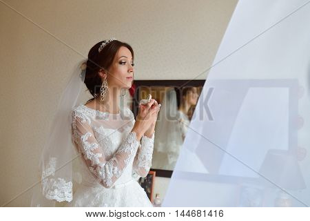 Beautiful sensual bride preparing for wedding ceremony and applying Perfume