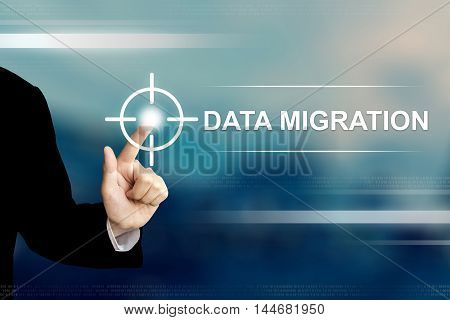 business hand pushing data migration button on a touch screen interface