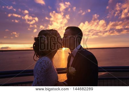 Harmonious beautiful bride and groom holding kissing at colorful magenta sunset on the observation deck