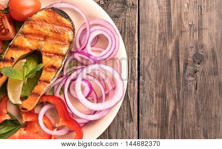 Grilled salmon steak with sliced onion and tomatoes on old wooden table top view at left side
