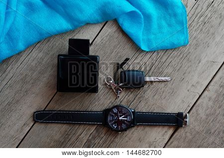 Men's Accessories. Male perfume, keys, watches, and a blue scarf on a wooden background