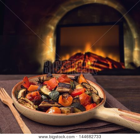 Grilled vegetables on serving pan and fireplace