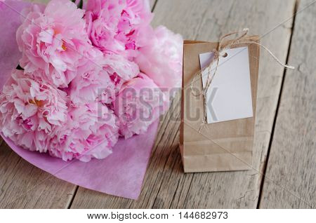 Kraft bag with tag for recording on a wooden table next to a pink peony
