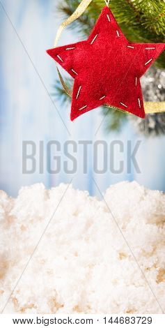 Handmade felt red star hanging on fir-tree branch from right top corner of light blue background vertical