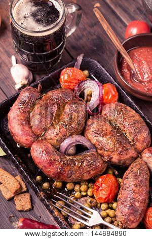 Homemade grilled sausages with pea and tomatoes on table closeup.Toned