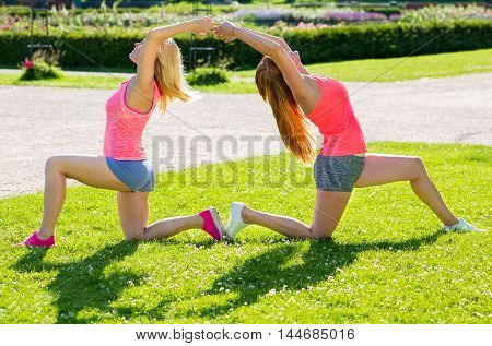 Fit ladies in gray shorts and bright red tops practicing yoga poses in a synchronized method outside at park