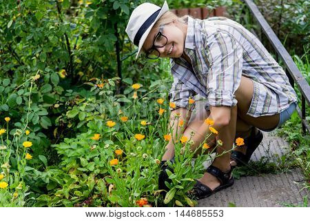 Young smiling girl in hat and glasses gardener grows flowers in her garden