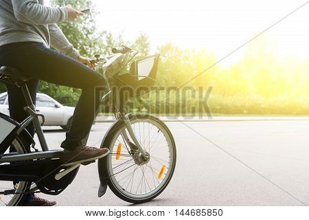 Guy sitting on bike with smartphone, image with copy space and lens flare effect