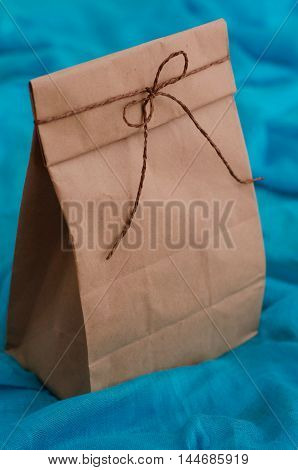 Package for lunch on a blue background. Gift kraft bag tied with twine