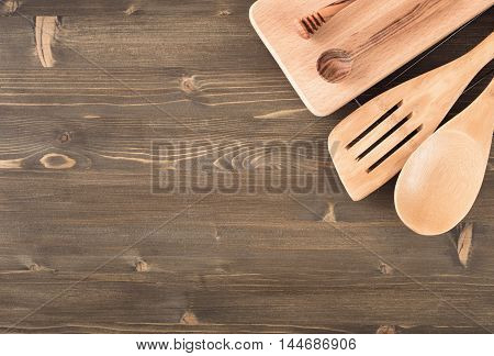 Kitchen utensils at top right corner of wooden background top view