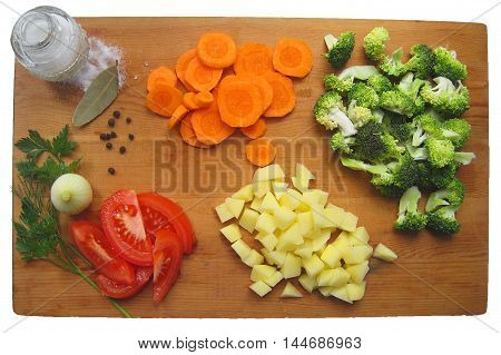 Sliced fresh vegetables on wooden cutting board. Healthy food: tomatoes, broccoli, potatoes, carrots, parsley, onion and salt isolated on white background