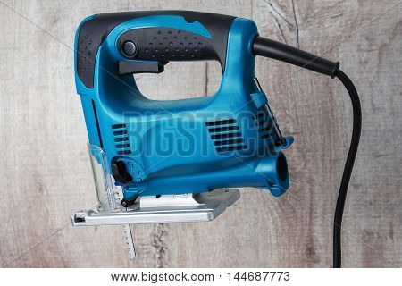 blue electric fretsaw on a wooden background isolated