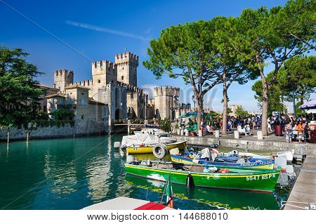 Sirmione, province of Brescia, Lombardy, northern Italy, 15th August 2016: people visiting the medieval castle Scaliger on lake Lago di Garda