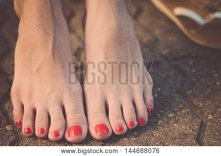 Female feet with red nail polish barefoot on the sidewalk (vintage)
