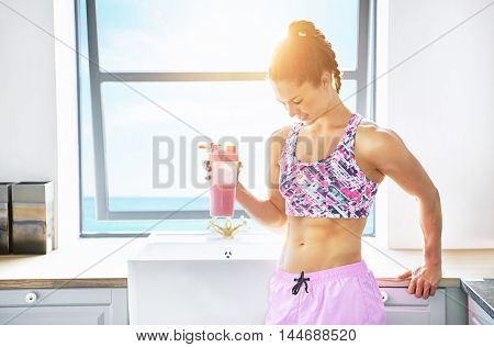 Fit young woman enjoying a glass of freshly squeezed fruit juice in a bright light clean kitchen in a healthy diet and lifestyle concept with copy space