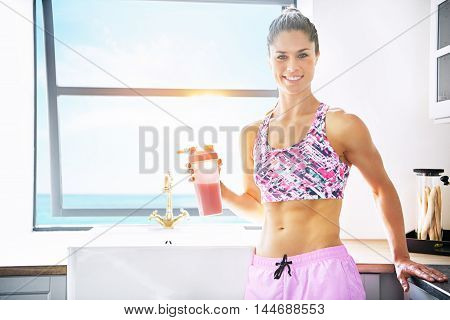 Pretty vivacious shapely fit young woman drinking fruit juice in a bright clean kitchen in a healthy lifestyle and nutrition concept with copy space