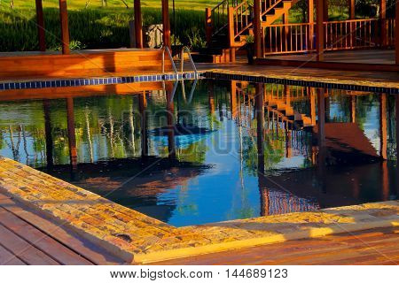 staircase and reflection in the water near swimming pool