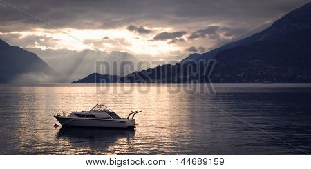 Boat on Lake Como at the sunset. Silver linings in Lake Como at the sunset. Retro style photo. Sunset view of the lake in Lombardy. Varenna Lake Como Italy.