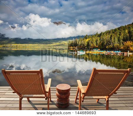 Pyramid Mountain reflected in Pyramid Lake. Two comfortable wooden sun beds for tourists, interconnected table