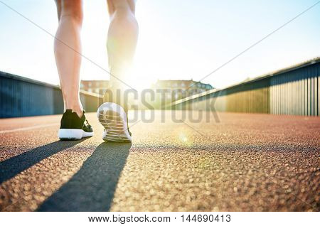 Low angle view of bare legs wearing running shoes facing apartments as the sun recedes behind them