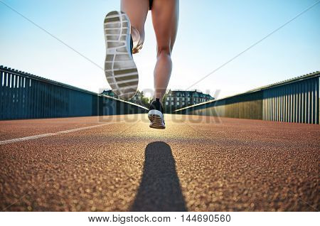 Bare legged jogger bounds towards apartments down empty road under a clear blue sky